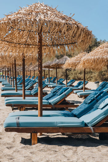Lounge chairs on beach against clear blue sky