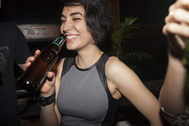 Smiling young woman drinking beer at bottle