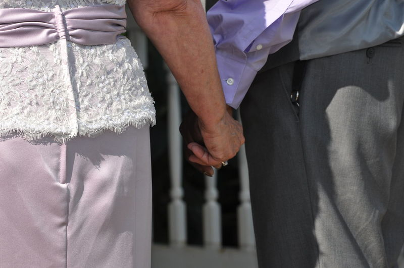Older Interracial Couple Getting Married and Holding Hands African American Couple Holding Hands Man Woman Bride Caucasian Celebration Close-up Groom Human Hand Interracial Life Events Midsection People Real People Standing Togetherness Two People Wedding Wedding Dress