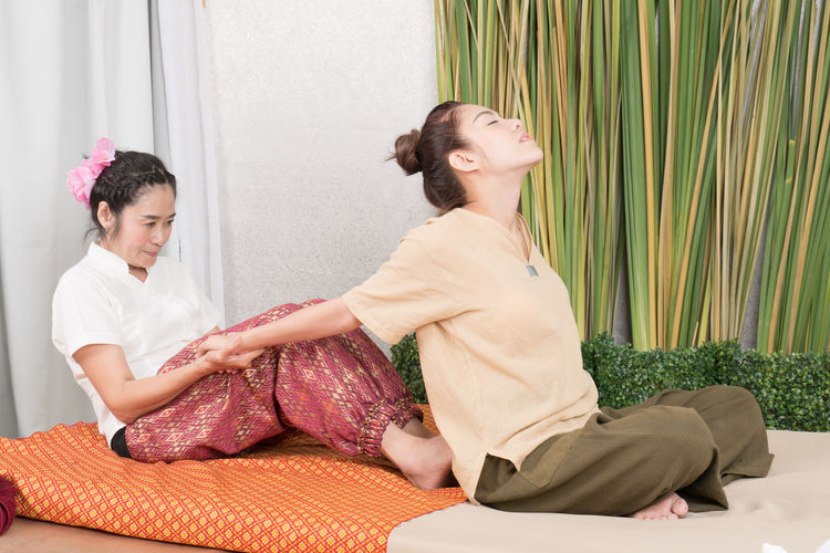Woman giving back massage to customer at spa