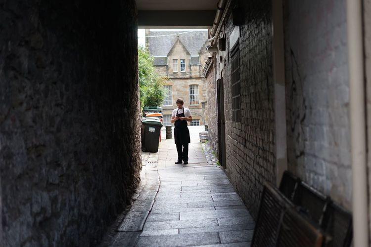 Rear view of man walking in alley amidst buildings