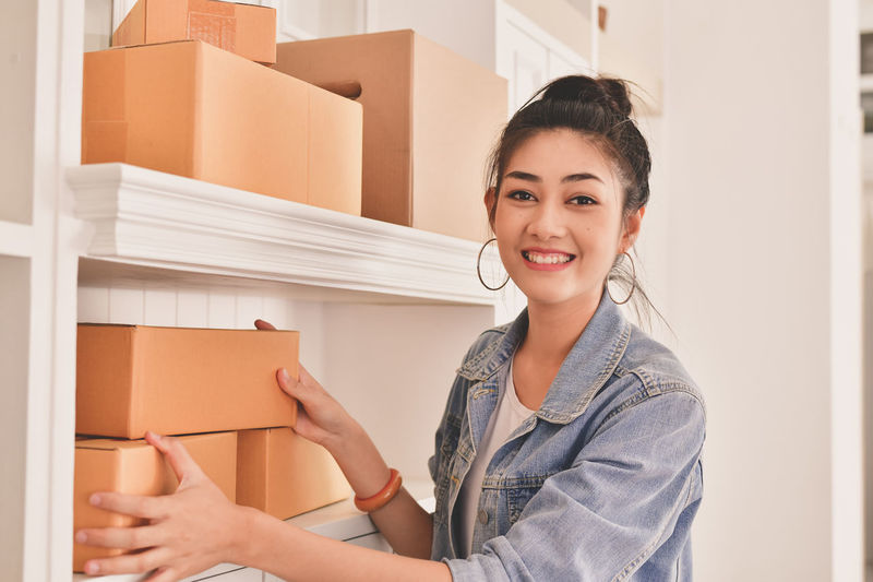 Beautiful Woman Box Box - Container Cardboard Cardboard Box Casual Clothing Container Front View Happiness Holding Indoors  Lifestyles Looking At Camera Moving House One Person Packing Portrait Smiling Waist Up Women Young Adult Young Women