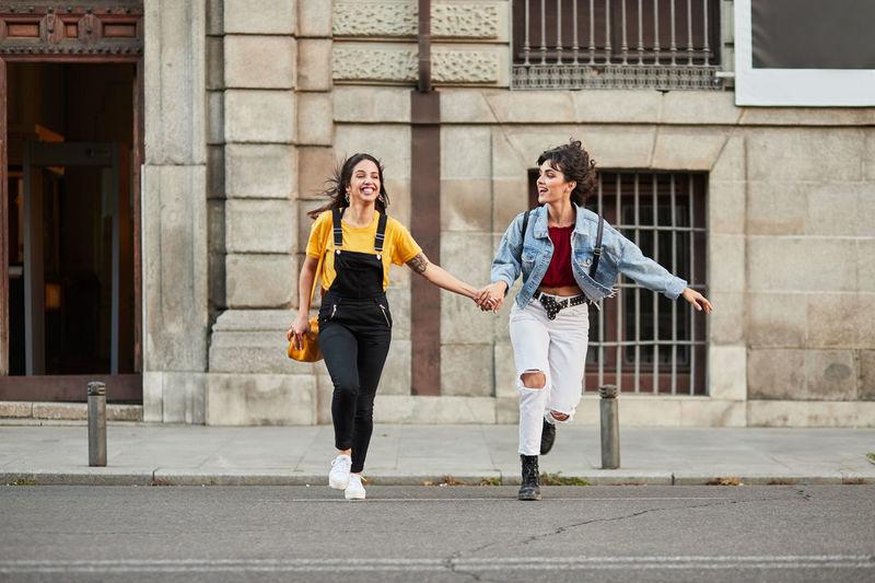 Full length of women holding hands running on road against building