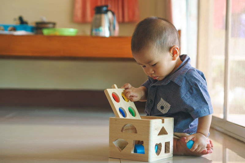 A year old Asian baby playing wooden toy box Childhood Child Innocence One Person Baby Indoors  Young Real People Boys Toy Block Toy Playing Babyhood Casual Clothing Home Interior Men Holding Males  Box Learning Development Brain Improve Asian  Solve