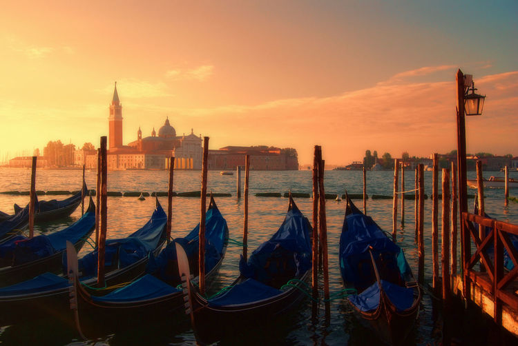 Gondolas Moored In Grand Canal Against St Mark Square Against Sky During Sunset