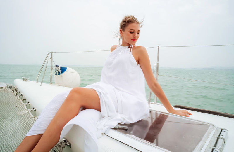 Woman sitting on boat against sea