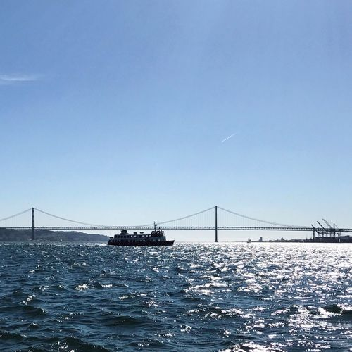 View of suspension bridge over sea against clear sky