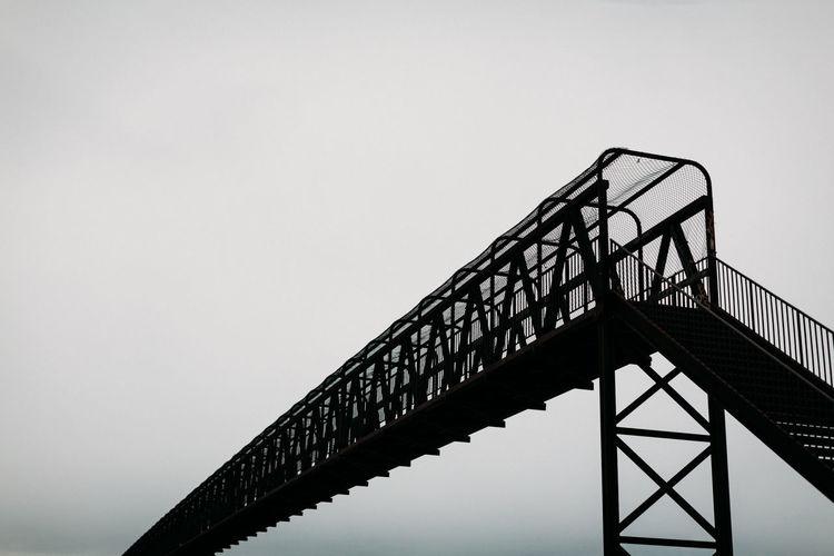 Silhouette of iron bridge against grey sky.