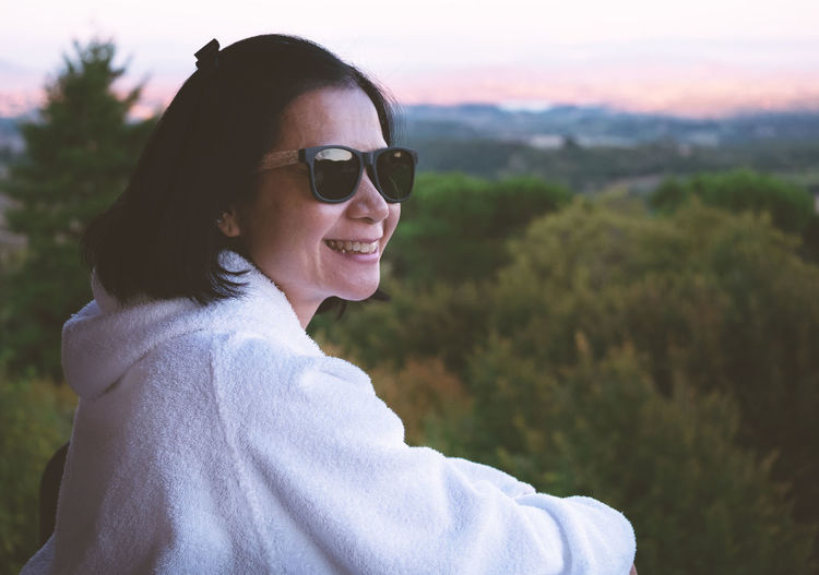 Side view of smiling woman wearing sunglasses standing against trees in balcony during sunset