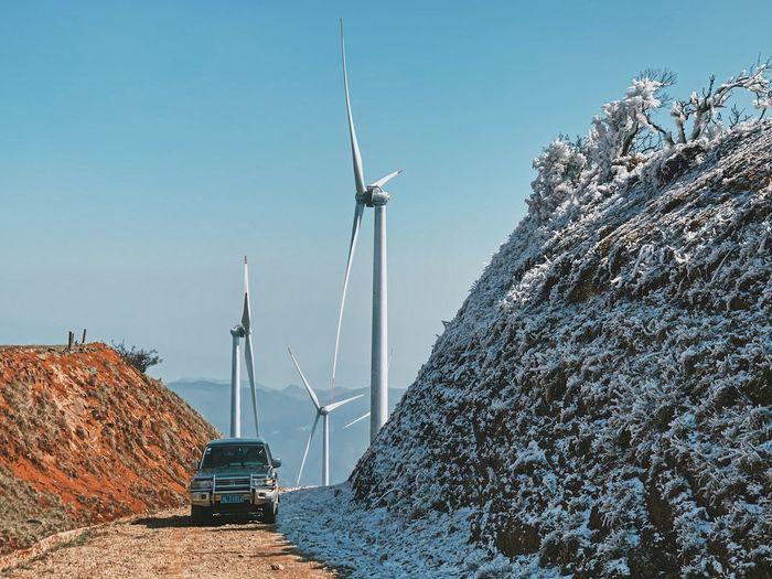 Wind turbines on rocks against sky