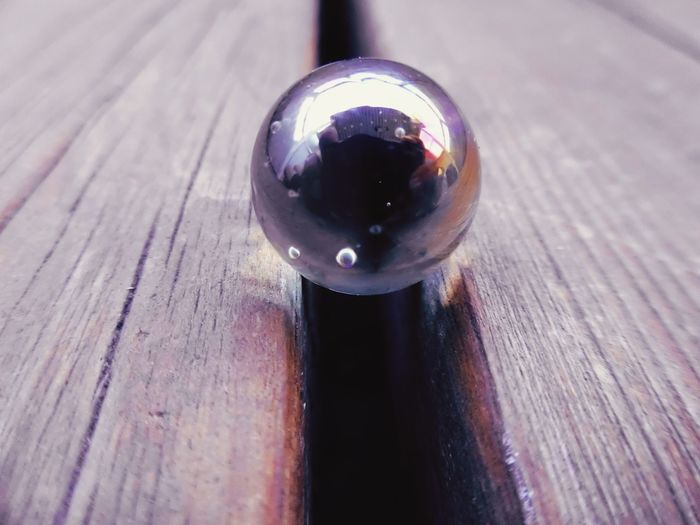 Close-up of metallic ball on wooden table