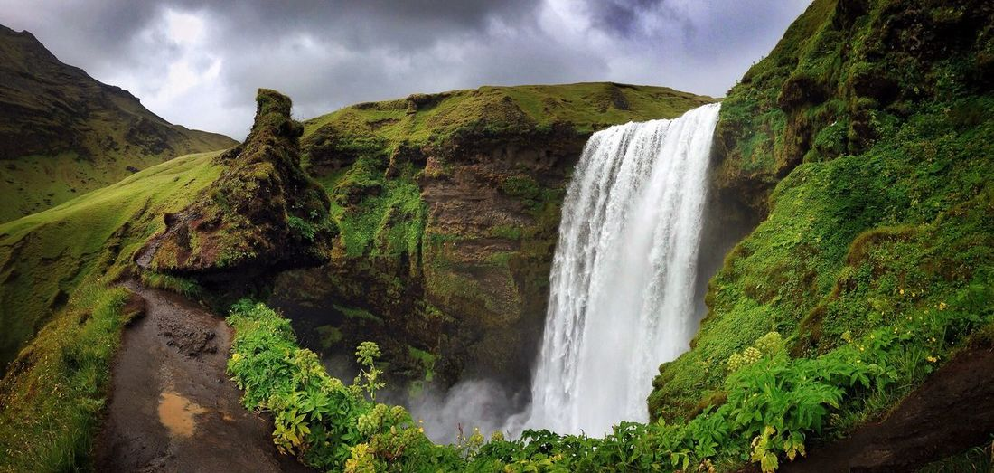 Scenic View Of Skogafoss Waterfall Against Cloudy Sky