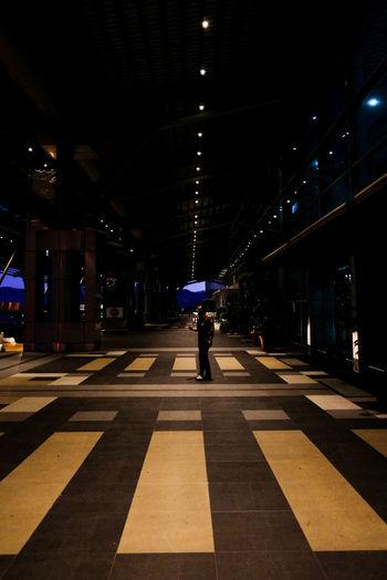 Man walking on illuminated road at night