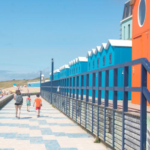 Rear view of people walking on railing against blue sky