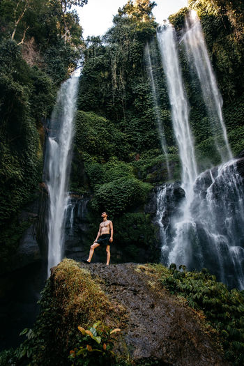 Man standing on rock against waterfall in forest