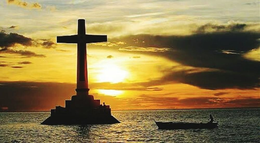 Sunset Dramatic Sky Cross Water Architecture Outdoors this is the cross of a church. It shrunk after a terrible deluge. Underwater is a cementery. A wide cementery. Corals and a good matrine life sanctuary.