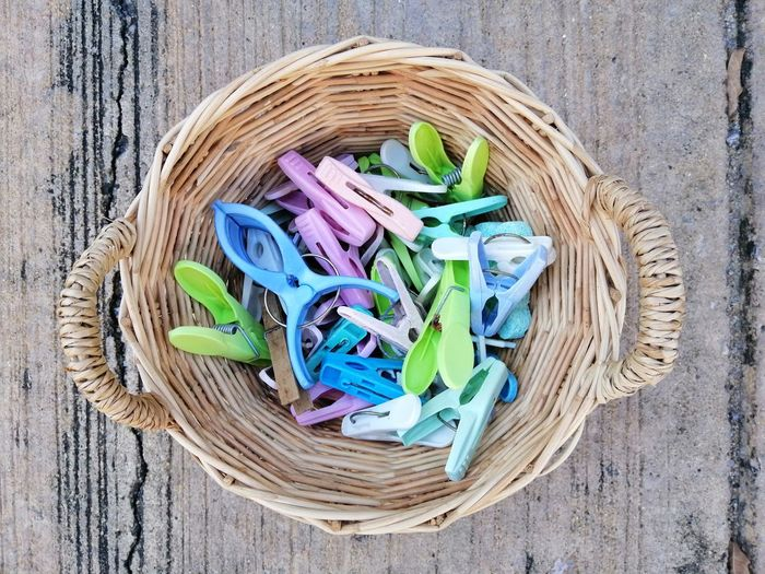 Plastic Cloth Clips in wicker baskets Fabric Outdoors Colorful Concrete Floor Handle Wicker Baskets Cloth Clips Plastic Equipment Household Cloth Clamp Clothespin Multi Colored Basket Choice High Angle View Directly Above Close-up Tool Hand Tool Clip