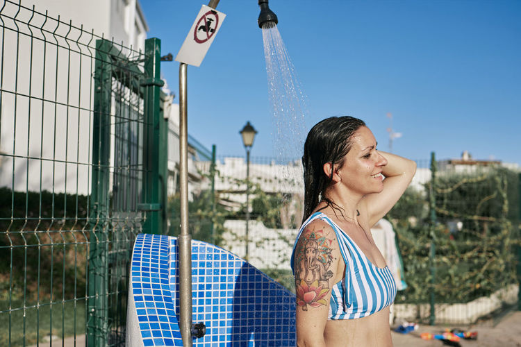 A young girl in a bikini showering in the pool. holiday concept