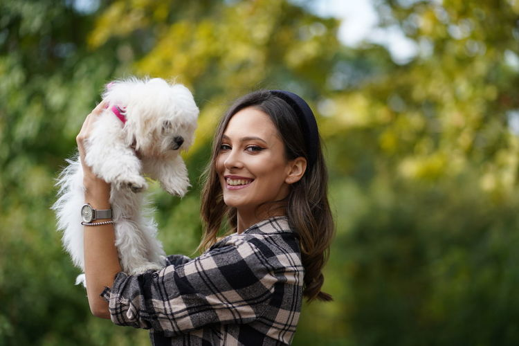 Portrait of smiling woman carrying dog