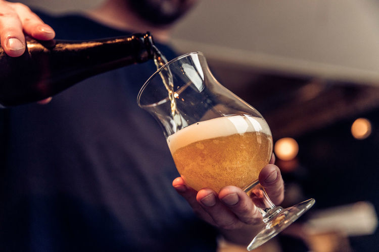 Midsection of man filling wineglass with beer