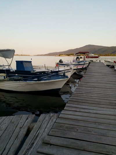 Boats moored in lake against clear sky during sunset