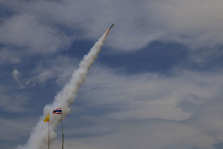 Low angle view of rocket flying against sky