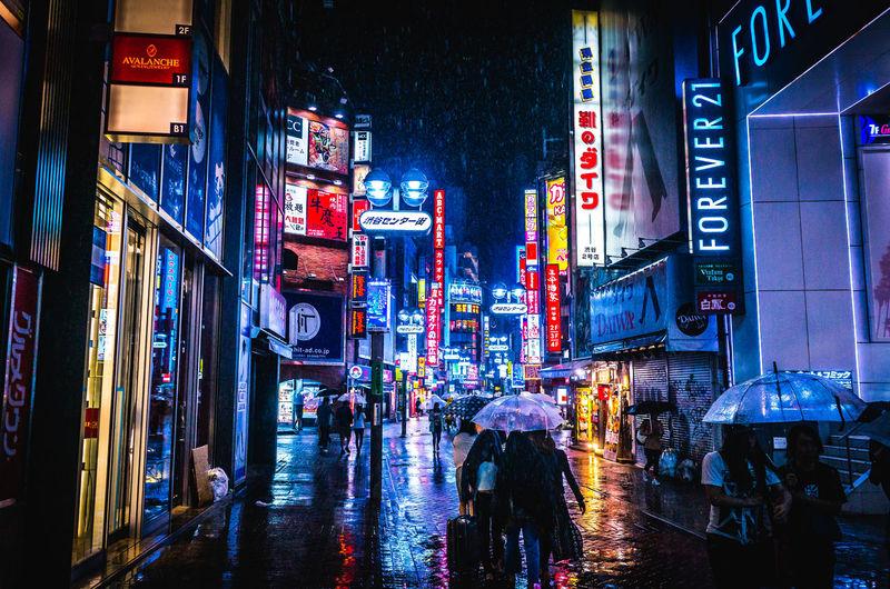 People on street amidst illuminated buildings during rainy season at shibuya