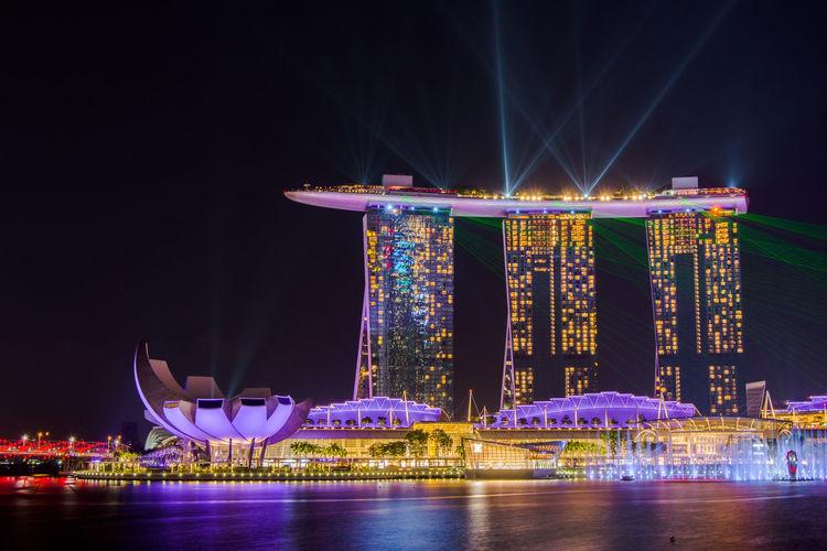 Illuminated marina bay sands in city at night
