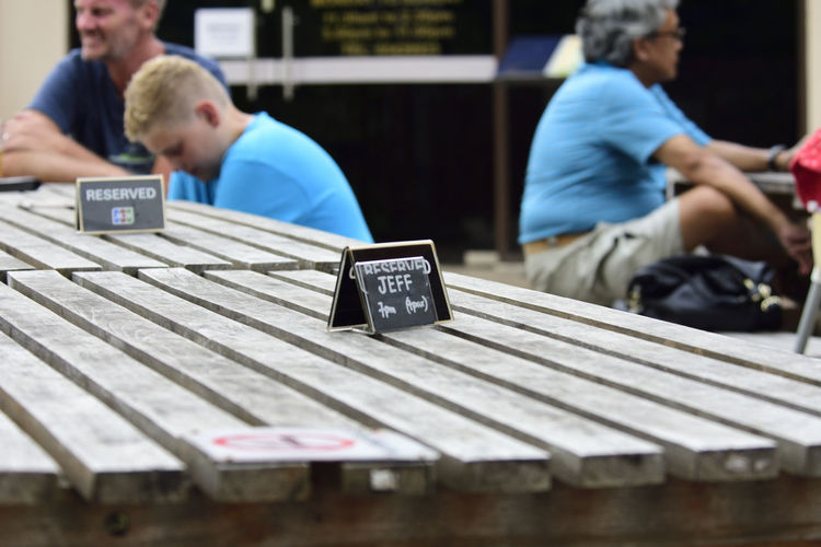 Close-up of label on table with people in background