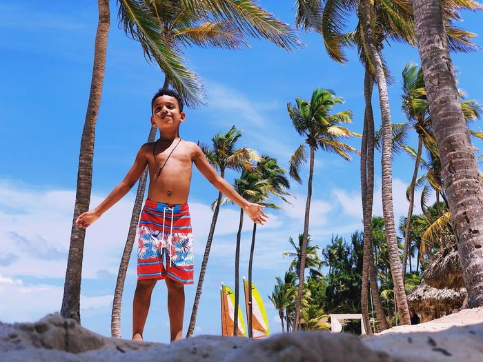 Portrait Of Shirtless Boy Standing At Beach Against Palm Trees
