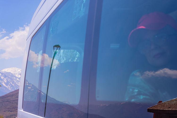 Woman sitting in bus seen through window