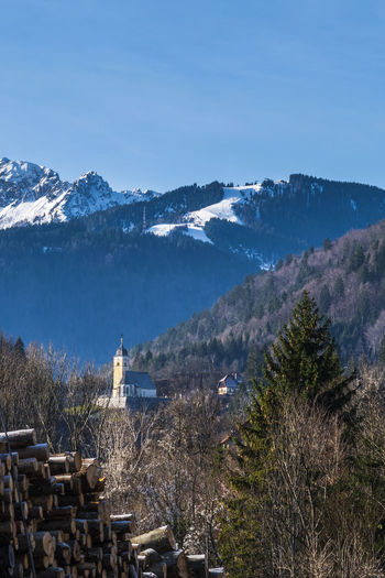 Coccau church and lussari ski slopes in the background. tarvisio in winter to be discovered. italy