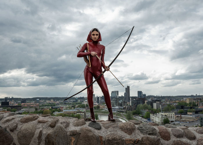 Portrait of woman holding bow and arrow while standing on retaining wall against sky