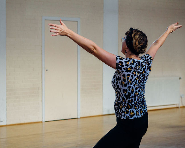Woman with arms outstretched dancing on hardwood floor at studio