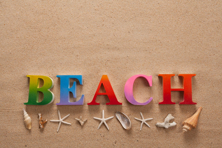 top view of beach written in colorful letters decorate with shellfish on the beach with copy space Alphabet Beach Capital Letter Communication Creativity Holiday Indoors  Land Letter Message Multi Colored No People Red Sand Single Word Studio Shot Text Trip Western Script