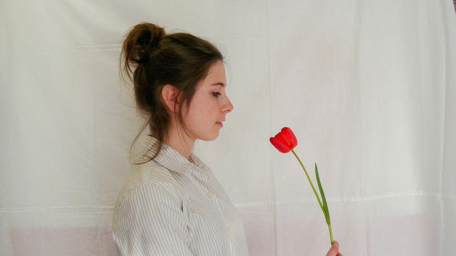 Woman holding red rose against white wall