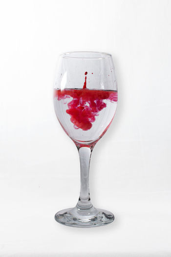 Close-up of red wine glass against white background