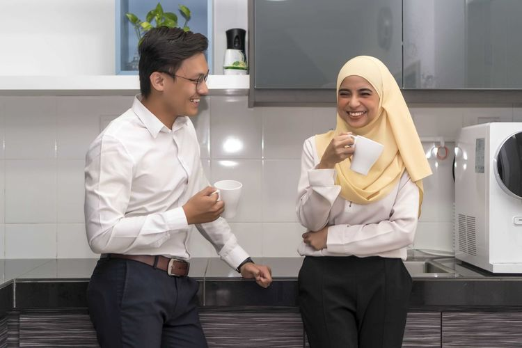 Two young executive malay having a break at pantry Young Adult Front View Three Quarter Length Standing Two People Real People Adult Young Women Holding Men Smiling Young Men People Indoors  Casual Clothing Clothing Women Occupation Males