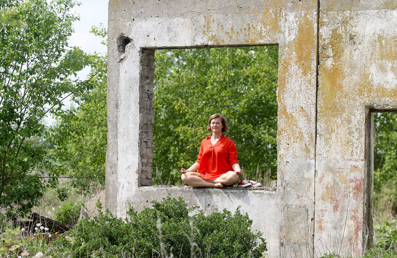 Woman sitting on stone wall by trees