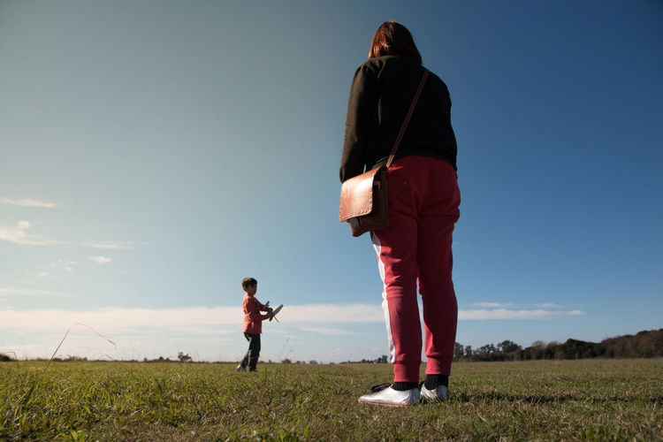 Mother and son on land against sky