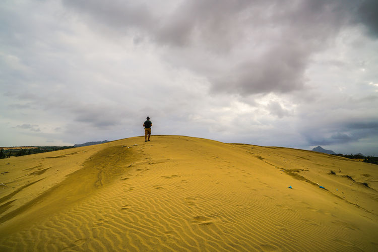 Rear view of man walking on sand dune at desert against cloudy sky