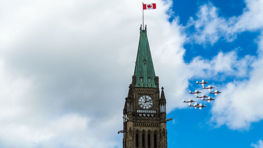 Royal Canadian Air Force flypast the Peace Tower on Canada Day Sky Cloud - Sky Low Angle View Day No People Outdoors Event Ceremony Canada Canada Day Ottawa Military Military Airplane Summer Summertime July Aerobatics Aerospace Industry Formation Formation Flying Blue Blue Sky Architecture Parliament Building Parliament Light Daylight Sunlight Airplane Air Vehicle Aircraft Aircraft Wing Speed Tower Built Structure Building Exterior Clock Tower Building Time Travel Destinations Tall - High City Travel Flag Government Wind Colors Beauty Clock Maple Leaf