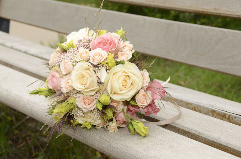 bouquet of wedding flowers lying on a wooden bench Accessory Bouquet Bunch Of Flowers Celebration Close-up Day Event Flower Flower Arrangement Flower Head Fragility Freshness Life Events Nature No People Outdoors Plant Romantic❤ Rosé Rose - Flower Wedding Wedding Ceremony