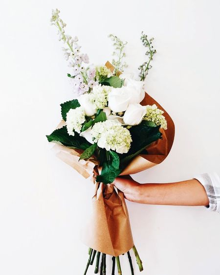 Cropped Image Of Woman Holding Bouquet Against White Background