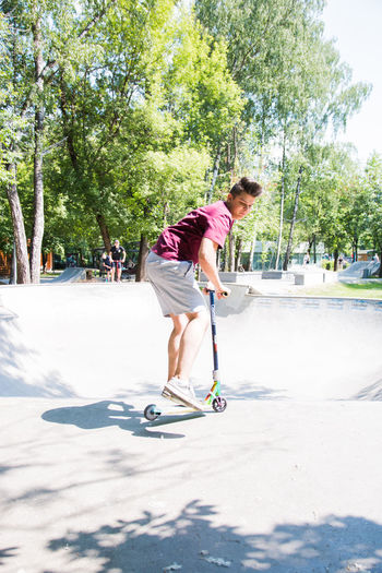 boy riding a scooter in a skatepark Tree One Person Full Length Nature Plant Leisure Activity Sunlight Day Casual Clothing Young Adult Young Men Real People Lifestyles Sport Shadow Growth Motion Outdoors
