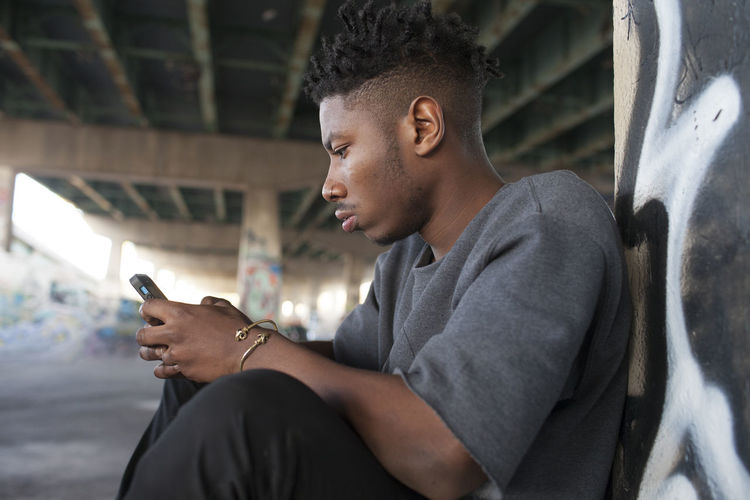 Side view of young man sitting outdoors