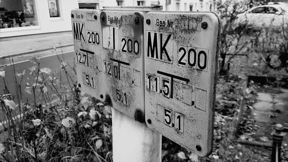 Focus On Foreground Day Outdoors No People City Close-up Sign Water Sign Street Streetphotography Background Blackandwhite Black And White Numbers First Eyeem Photo Low Angle View Another Angle Another Angle Another View