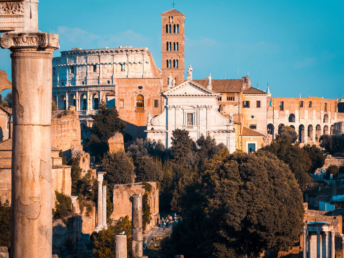 Buildings in city against sky, coloseum and rome
