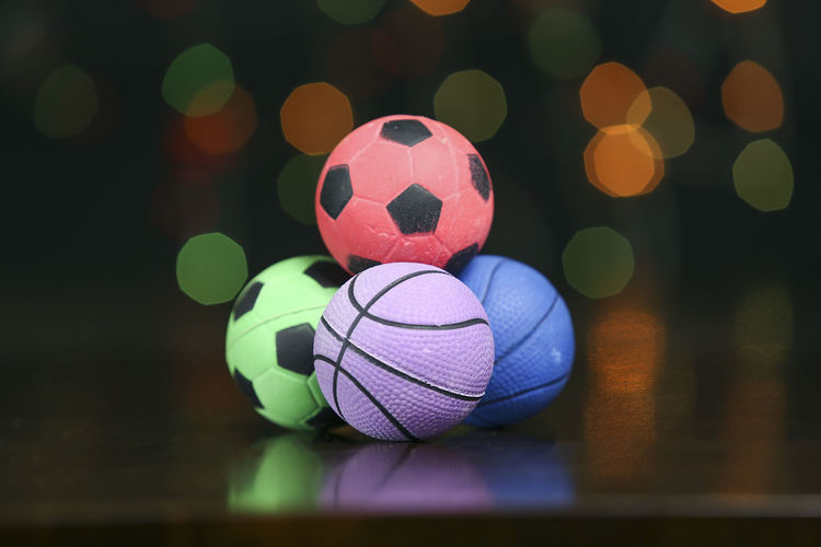 Rubber ball in wooden table with light blur background Toys Art And Craft Ball Close-up Design Focus On Foreground Game Indoors  Multi Colored No People Pattern Pink Color Rubber Ball Selective Focus Shape Soccer Soccer Ball Sphere Sport Sports Equipment Still Life Team Sport Toy Toy Photography