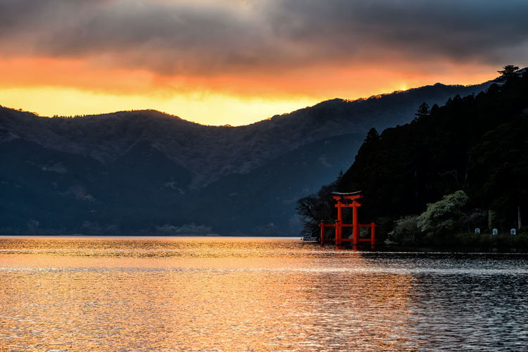 Red torii gate statue at Lake Ashi of Hakone shrine with twilight sky and sunlight reflection on water, Japan. Here is the famous travel landmark for visitor to sightseeing from Pirate tourist ship. Ashi Lake Torii Gate Architecture Beauty In Nature Built Structure Cloud - Sky Hakone Idyllic Lake Lake View Mountain Mountain Range Nature No People Orange Color Scenics - Nature Sky Sunset Tranquil Scene Tranquility Water Waterfront